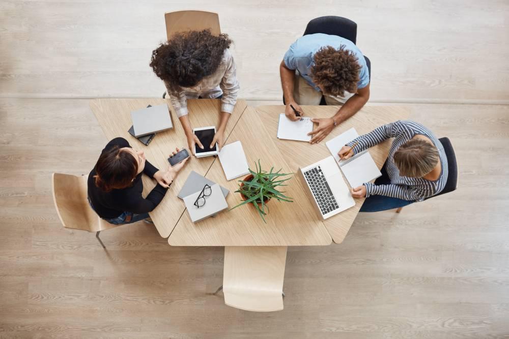 Slika iz ptičije perspektive radnog stola u kancelariji za kojim sede 4 osobe i imaju timski sastanak