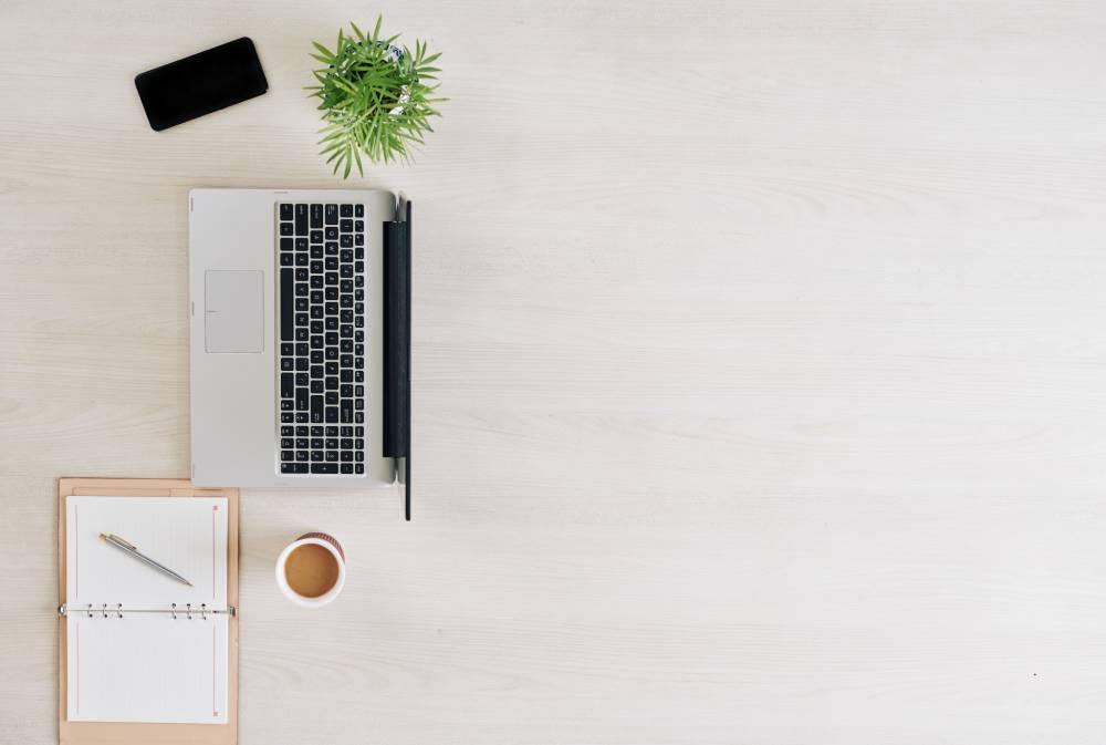 Slika drvenog stola iz ptičije perspektive na kome se nalazi otvoren laptop, sveska, olovka, telefon i biljka u saksiji