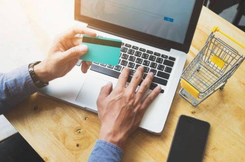 Osoba za laptopom, sa karticom u rukama na web shopu spremna za kupovinu