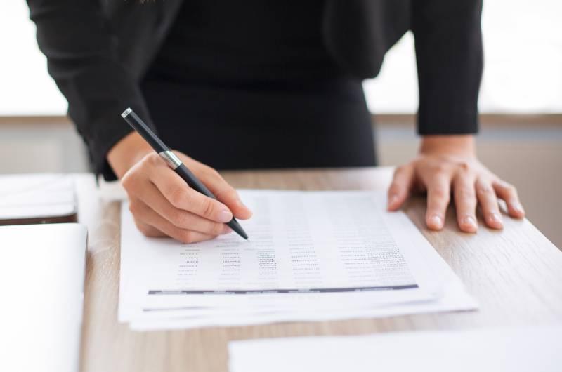 Osoba za stolom koja drži olovku i papir i priprema se za inspekcijski nadzor