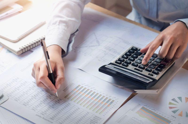 Osoba za stolom koja se bavi računovodstvom i vodi evidenciju online prodaje i naplate