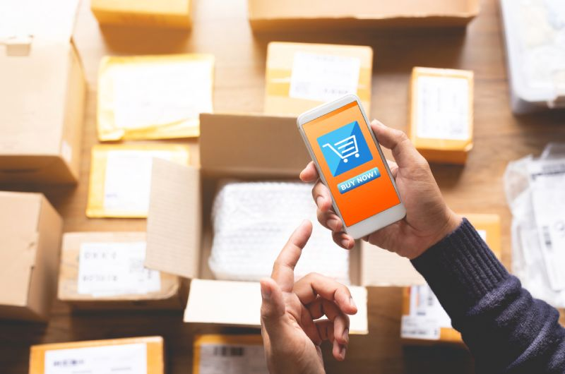 Muške ruke koje drže telefon i dvoume se da li da odustanu od online kupovine