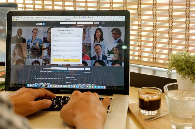 Osoba za laptopom koja uređuje linkedin poslovni profil i pravi reklame za oglašavanje