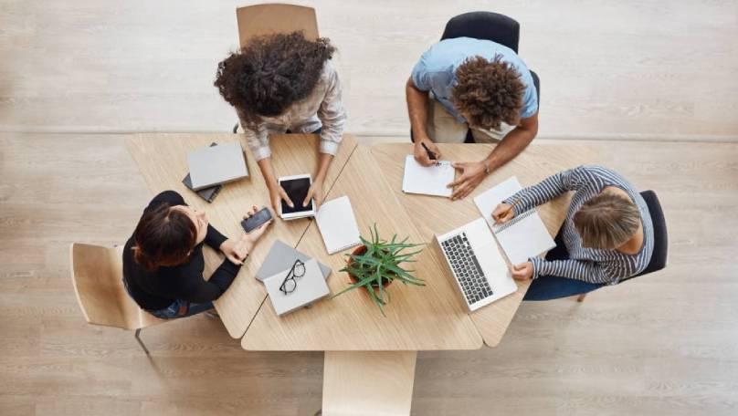 Slika ljudi za stolom koji se usavršavaju na online seminaru