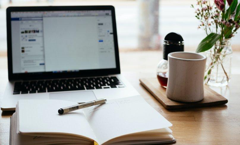 Pripremljen sto za online sastanak sa laptopom, sveskom i olovkom