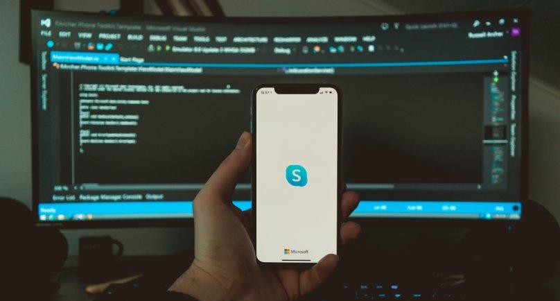 Ruka koja drži telefon na kome je upaljen skype putem koga se odvija sastanak ispred velikog ekrana