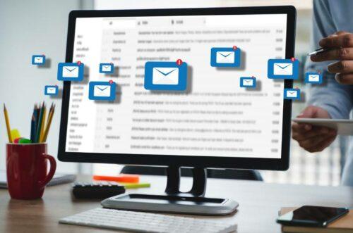Ekran računara sa plavim ikonicama mailova koji izlaze iz njega