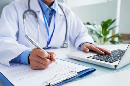 Doktor za laptopom proverava da li je došlo do zloupotrebe bolovanja