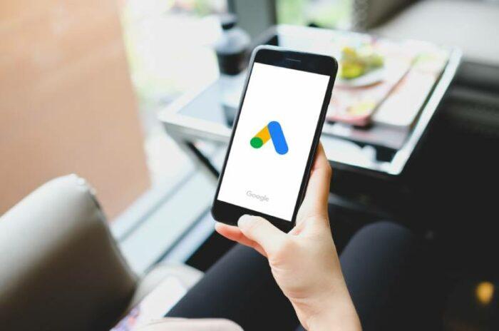 Devojka koja drži telefon sa otvorenom Google Ads aplikacijom