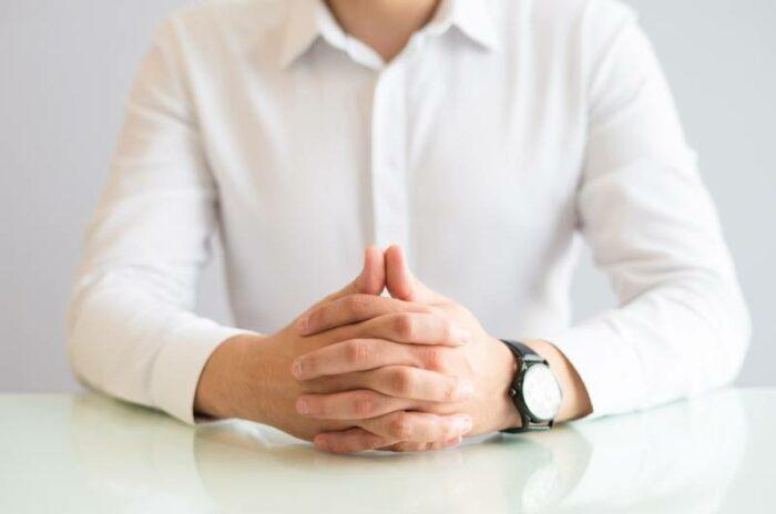 Čovek u košulji sedi prekrštenih ruku i ponaša se u skaldu sa zakonom na radnom mestu